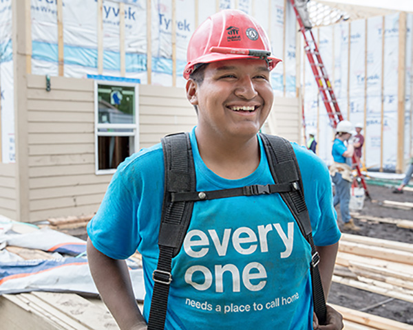 An AmeriCorps member poses in front of a home build, photo courtesy HFHI