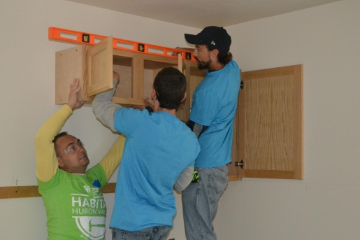 Volunteers with Habitat for Humanity Huron Valley install cabinets provided by the Prison Build Program