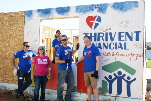 Volunteers with Thrivent Financial pose in front of decorated wall panel