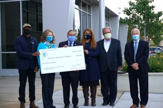 Six individuals stand together wearing masks and holding a ceremonial check