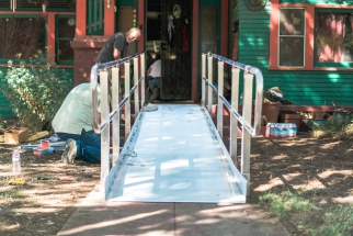 Two men assemble a metal wheelchair ramp leading into a green house with red trim
