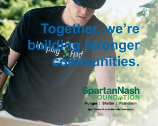 "SpartanNash volunteers working at a Habitat build site with text saying ""Together we're building stronger communities"" and SpartanNash logo"