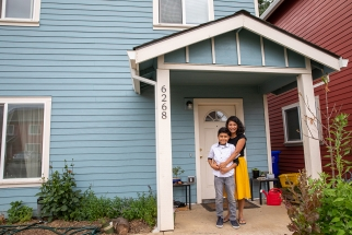 A woman and her son stand in the doorway of their new Habitat Home
