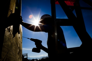 backlit volunteer uses power drill on side of build site
